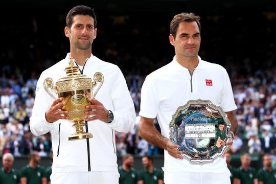 El campeón Novak Djokovic de Serbia, y el subcampeón Roger Federer de Suiza, posan con sus respectivos trofeos en la final de Wimbledon.