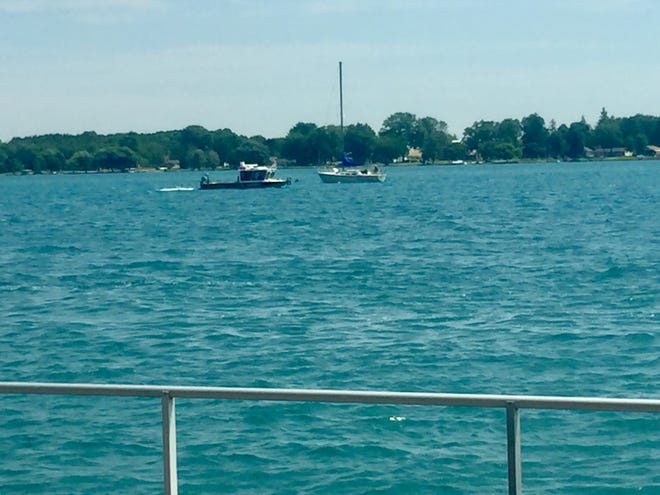 A sheriff boat passes the St. Clair boardwalk while searching for missing 21-year-old Riley Gleason. He was last seen entering the water off a boat near the St. Clair Inn Saturday.