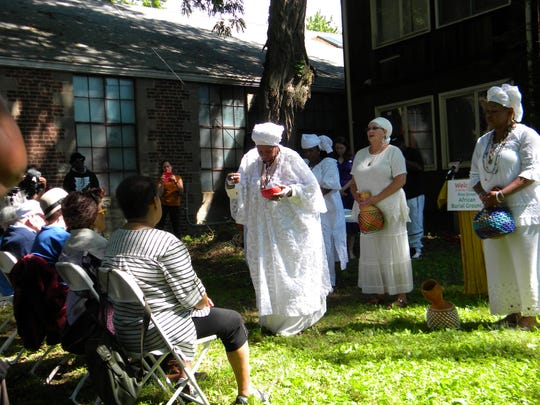 Miss V of the Good Gourd group blesses the site of the Pine Street African Burial Grounds that date to the 18th century during the June 15 ceremony at 157 Pine St. in Kingston.