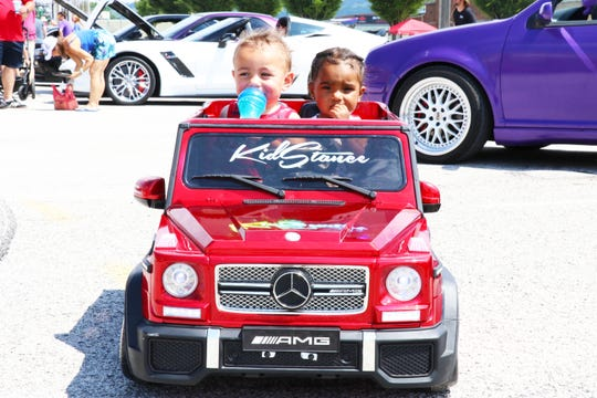 Darwin Ippolito (left) and Jessenyiah Lizardo (right) pose in a miniature car at the York Expo Center, on Sunday, June 14.