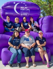 Representatives from the Greater Nevada Credit Union pose for a photo on a giant inflatable chair.