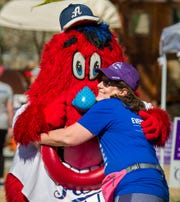 January L'Angelle, of Fernley, hugs Reno Aces mascot Archie after finishing the cancer survivors' lap.