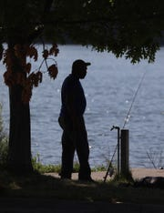 James Lewis of Rochester keeps cool by fishing in Irondequoit Bay in the shade of the tree. Areas on and around the Irondequoit Bay Outlet Bridge are popular year-long fishing spots.