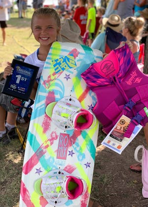 Berkley Otho, a 9-year-old from Christoval, displays her first-place plaque and prizes won at the Wake the Desert 2019 wakeboard competition July 12-14 in San Angelo.