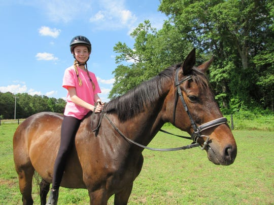 Olivia Wheatley of Maryland rides Toby. She says she fell in love with the Chincoteague ponies during a visit to the island refuge.