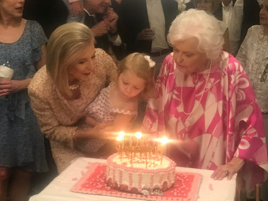 Ginny Simmons and a young child help Simmon's mom, Ann Walke, blow out candles on her 90th birthday cake.