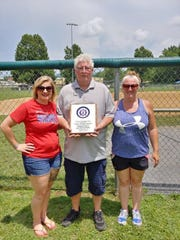 "Brandi Moomau, Rocky Moomau and Candace Moomau accept a plaque on behalf of the late Lionel ""Rabbit"" Moomau, who was inducted into the Babe Ruth Southeast Region Hall of Fame."