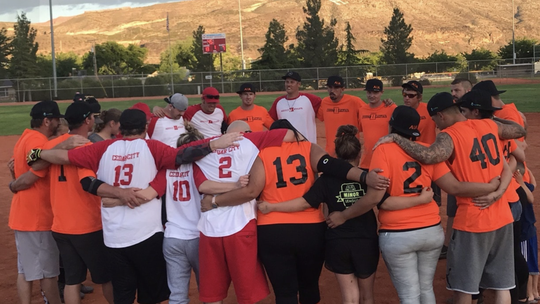 Players involved in the sober softball league huddle during a game. The softball league is comprised of recovering addicts in the Southern Utah area who use the sport as an outlet during their recovery process.