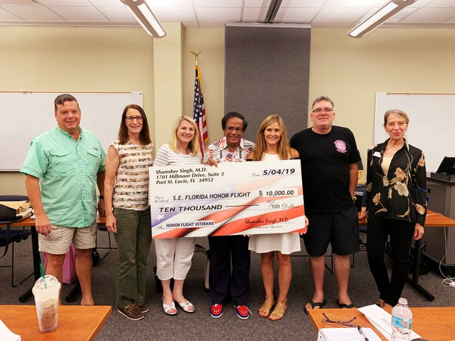 Dr. Shamsher Singh, center, presents his $10,000 memoriam gift to Southeast Florida Honor Flight. Pictured are, from left, Eric Stein, Denise Rousseau, Janet Hoose, Singh, Kathy Sreenan, Tom Shimanek and Donna True.