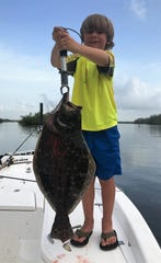 Ryder Burr, 6, of Hobe Sound caught his first redfish, a 20-incher, and his first flounder, this 23-incher, while casting gold spoons in the Intracoastal Waterway near the Crossroads.