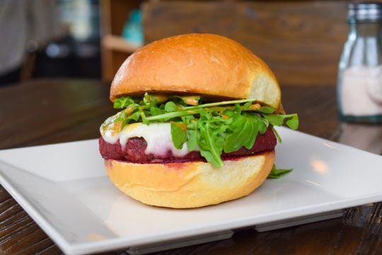 The Root Burger at Grass Roots Kitchen consists of a signature beet patty, vegan swiss, watercress, pickled onions, and GRK sauce.
