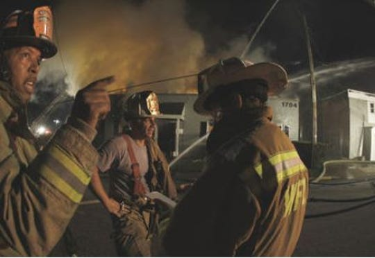Battalion Chief James Jobes (left) is pointing at something during a 2007 building fire.