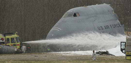Firefighters spray foam to a downed military C5 Galaxy in a field southeast of the Dover Airforce Base in Dover, Delaware on Monday April 3, 2006.