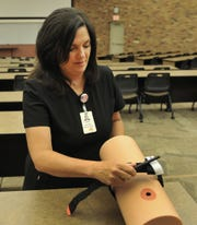 United Regional, trauma educator, Laura Pressler demonstrates the proper way to apply a tourniquet on a trauma simulator Monday afternoon at Midwestern State University.MSU Wilson School of Nursing and United Regional have joined together to help educate the public about what to do when dealing with a possible life-threatening injury.