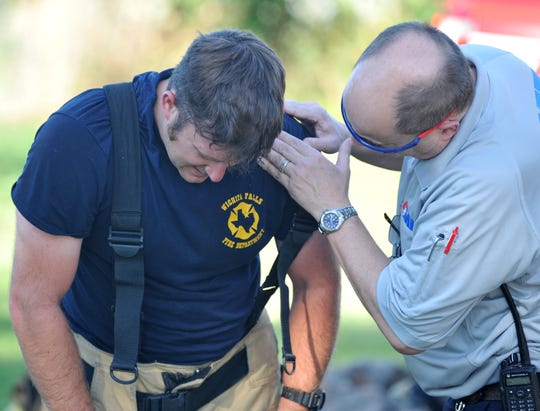 An AMR medical technician assists a Wichita Falls firefighter at the scene of a structure fire Sunday evening at a vacant house on the city's north side.