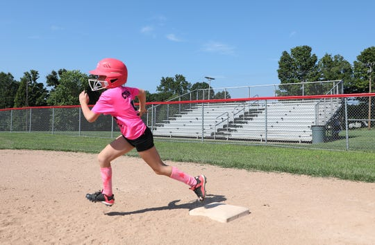 A camper races around first during Muskingum University's softball camp in New Concord on Monday.
