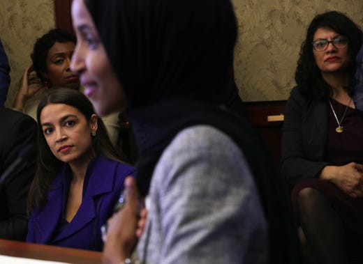 Alexandria Ocasio-Cortez and Rashida Tlaib listen to Ilhan Omar speak during a congressional Iftar event at the U.S. Capitol May 20, 2019 in Washington, DC.