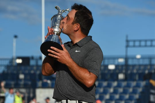Francesco Molinari kisses the trophy as he poses for pictures with the Claret Jug, the trophy for the Champion golfer of the year after winning the 147th Open golf Championship at Carnoustie, Scotland, on July 22, 2018.