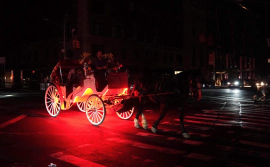 A horse drawn carriage drives past 7th Avenue.