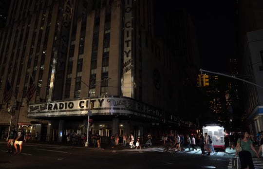People walk past Radio City Music Hall in the dark.