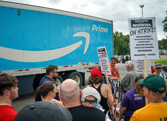 Workers, supporters and activists picket outside the Amazon fulfillment Center in Shakopee, Minn. on the afternoon of Prime Day, Monday, July 15, 2019. Trucks were allowed through the picket line after a brief delay.