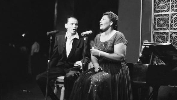 Ella Fitzgerald and Frank Sinetra share a stage as the sing one of their many duets in 1958.