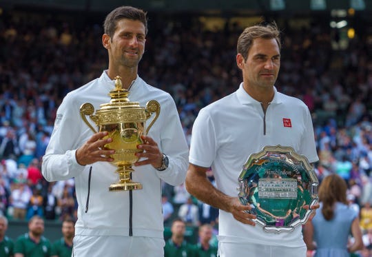 Novak Djokovic poses with the champion's trophy and Roger Federer the runner-up trophy after their marathon final at Wimbledon.