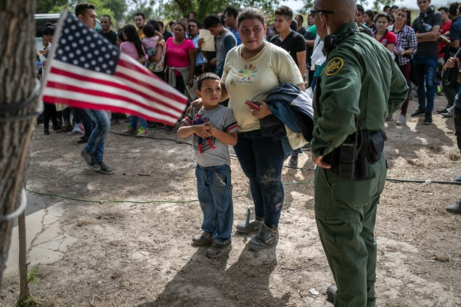 A U.S. Border Patrol agent speaks to immigrants after taking them into custody on July 2, 2009, in Los Ebanos, Texas.