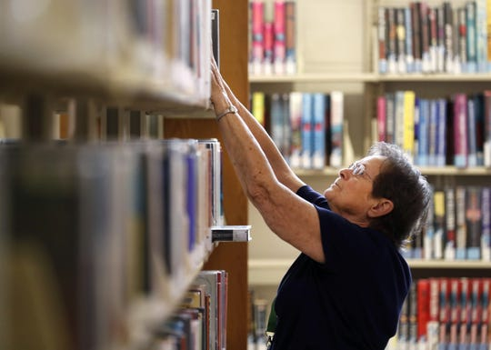 Volunteer Orien Kronberg reshelves books at the Appleton Public Library.
