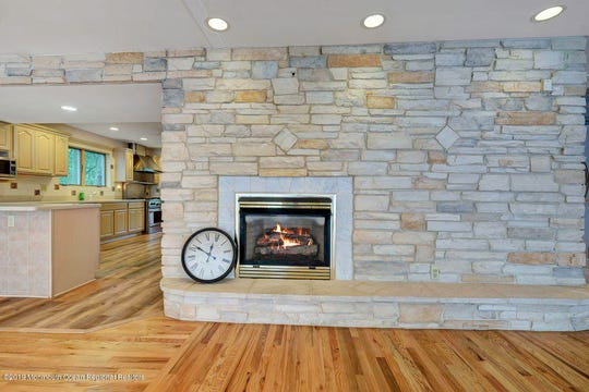 The living room features a stone wall with a fireplace and recessed lighting.