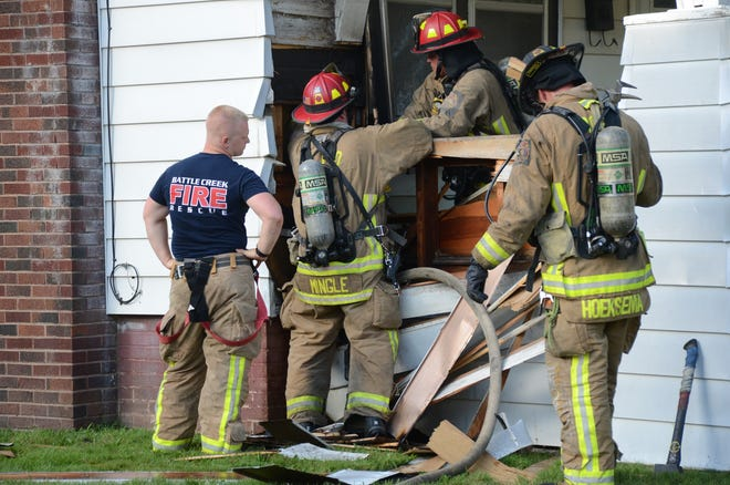Battle Creek firefighters search for flames after a fire began on a porch at 93 Lathrop Ave. on Monday.