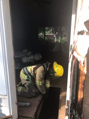 """Hayden Smallbeck, a firefighter with North Kitsap Fire and Rescue, removes a panel of flooring damaged by a fire in a Kingston home on Sunday evening. Homeowners were away but called 911 after their """"smart"""" smoke detector alerted them to the fire on a mobile device."""