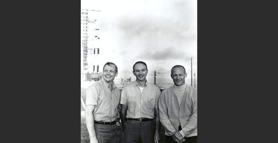 Apollo 11 astronauts Neil Armstrong, Michael Collins, and Buzz Aldrin are seen at Kennedy Space Center's pad 39A before their July 16, 1969 liftoff. In the background is their Saturn V rocket.