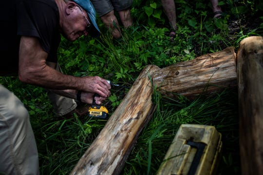 Eric Chittenden screws together two pieces of the base of a loon nesting raft in Stowe, VT, July 15, 2019.