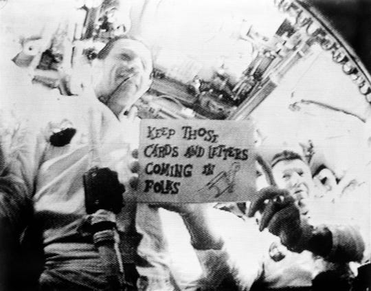 "Astronauts Walter M. Schirra Jr., mission commander (right); and Donn F. Eisele, command module pilot; are seen in the first live television transmission from space — made possible by tracking stations in Corpus Christi and Merritt Island, Florida. In the Oct. 14, 1968, broadcast Schirra is holding a sign which reads, ""Keep those cards and letters coming in, folks!"" Out of view at left is astronaut Walter Cunningham, lunar module pilot."