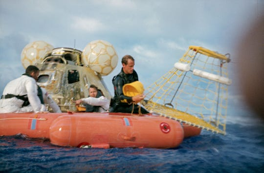 "Shown is a water-level view of recovery operations for the Apollo 13 mission in the South Pacific Ocean on Aug. 17, 1970.  The three crewmen had egressed their spacecraft, and were awaiting the readying of the ""Billy Pugh"" net — invented by Corpus Christi entrepreneur Billy Pugh — which would hoist them to a helicopter hovering above. The crewmembers (from the left) are astronauts Fred W. Haise Jr., lunar module pilot; John L. Swigert Jr., command module pilot; and James A. Lovell Jr., commander."
