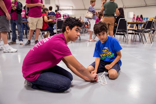 Teddy Trevino, left, 14, shows his brother, A.J. Trevino, 10, the catapult he built in the summer Corpus Christi Prefreshman Engineering Program at Del Mar College during a family day on Tuesday, July 16, 2019. The program is a local program for the statewide TexPREP initiative, of which the goal is to keep students engages in STEM activities during the summer months.