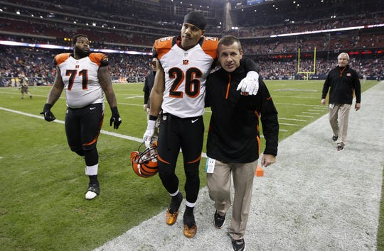 Cincinnati Bengals strong safety Taylor Mays (26) walks off the field with strength & conditioning coach chip Morton after their 19-13 loss to the Houston Texans in the first round of their AFC playoff game at Reliant Stadium in Houston, Texas in 2013