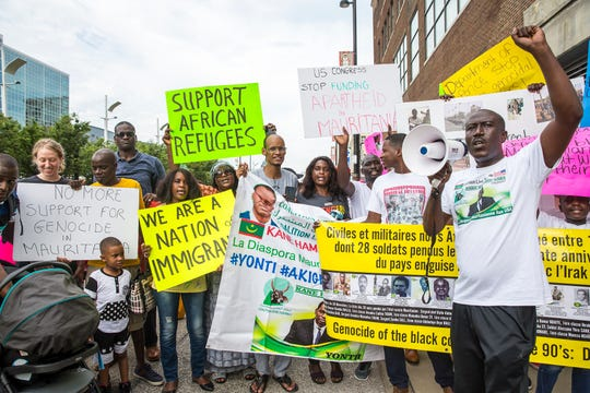 """Ibrahima Guisset chants """"What do we want?"""" The crowd yells, """"Justice."""" Members of the Mauritanian-American community and supporters march Monday through Downtown to protest what they say are human rights violations against Afro-Mauritanians in the northwest African nation."""