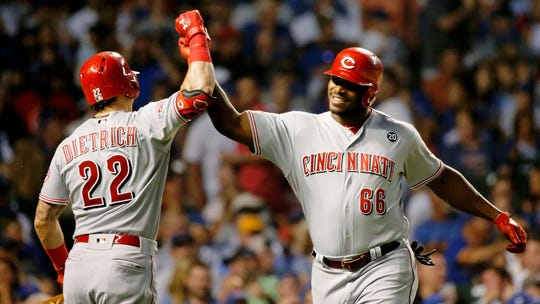 Jul 15, 2019; Chicago, IL, USA; Cincinnati Reds right fielder Yasiel Puig (66) smiles while congratulated by left fielder Derek Dietrich (22) for his home run against the Chicago Cubs during the sixth inning at Wrigley Field.