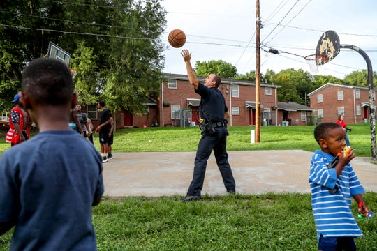 A Clarksville Police officer recovers the basketball to shoot with residents at Summer Night Lights on the block behind Caldwell Lane Head Start in Clarksville, Tenn., on Monday, July 15, 2019.