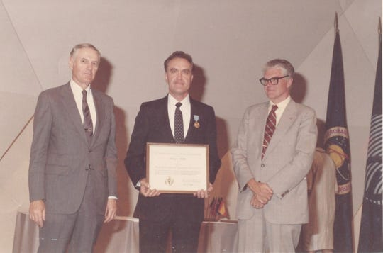 Gray Settle, center, receives the NASA Exceptional Engineering Achievement award at NASA Headquarters in Washington, D.C., for work done on the Spacelab program. At left is NASA Administrator James Beggs, and at right is Deputy NASA Administrator Hans Mark.