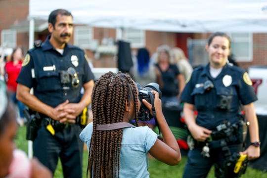 A resident points the camera and snaps pictures of police officers at Summer Night Lights on the block behind Caldwell Lane Head Start in Clarksville, Tenn., on Monday, July 15, 2019.