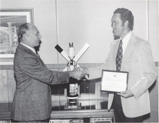 Helmut Hoelzer, left, a member of Wernher Von Braun's original team and director of the Computation Laboratory, presents Gray Settle with an award.