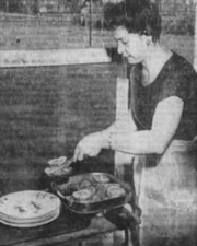 Mrs. Anson Vinall cooks over a skillet to avoid creating more heat on a hot day in  July, 1946.