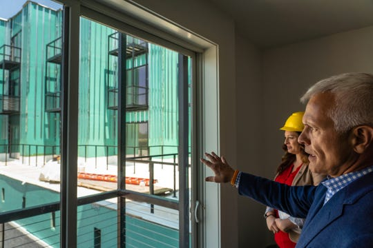 Eric Larson of Larson realty group and Karen Matkovich, Senior Area Director of Village Green talk about development while standing in an apartment at The Corner mixed-use development that sits on the site of the former Tiger Stadium on Michigan Ave. and Trumbull Ave. in Detroit's Corktown neighborhood on Monday, July 15, 2019.