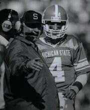 MSU head coach George Perles talks with a quarterback before a game against Indiana.