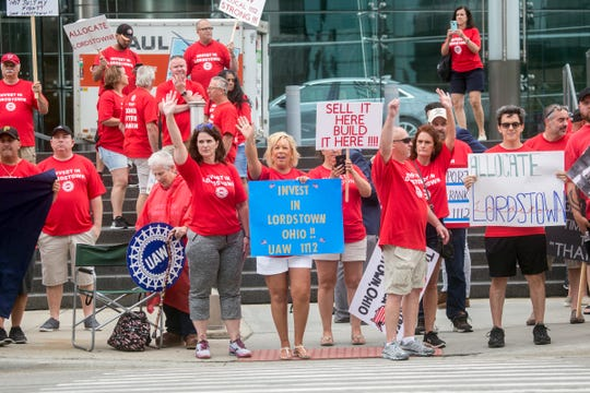 A group of UAW protesters wave to passing cars as General Motors and the UAW open 2019 contract talks for a new national agreement on Tuesday, July 16 at the Detroit Marriott Renaissance Center 2019.