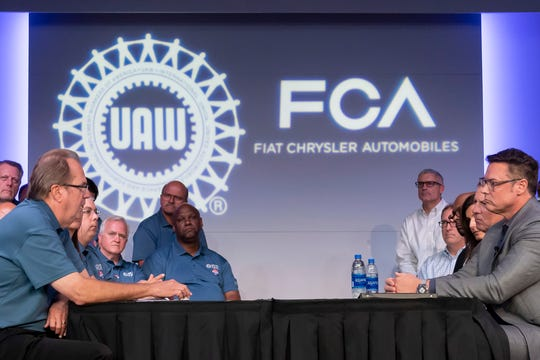 FILE -- The heads of the UAW and FCA sits at a table together before the ceremonial handshake to mark the beginning of negotiations between the United Auto Workers and Fiat Chrysler Automobiles at FCA's North America headquarters in Auburn Hills.