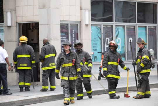 Detroit fire fighters monitor the situation after extinguishing a fire at Parc restaurant in Campus Martius Park in downtown Detroit Tuesday afternoon, July 16, 2019.